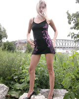 Slender blonde girl poses outdoor