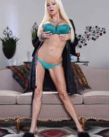 Blonde bombshell crosses her bare legs as she removes her bikini
