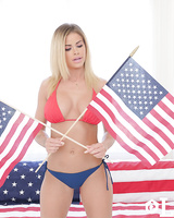 Solo model Jessa Rhodes oils up after stripping afore the USA flag