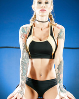 Tattooed female wrestler Sarah Jessie exposes her big tits and sexy tight body