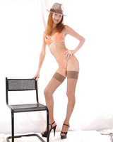 Ginger babe in hat poses on the chair