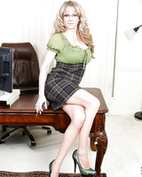 Chesty blonde MILF Elizabeth Green flashing leg and stocking tops on desk