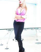 Bosomy blonde office babe in knee high black boots unleashes huge hooters