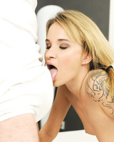 Tattooed blonde chick Angel Piaff sucks the jizz from a cock laying on her bed