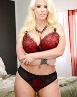 Thick blonde lady Alura Jenson takes off her bra and panties atop her bed