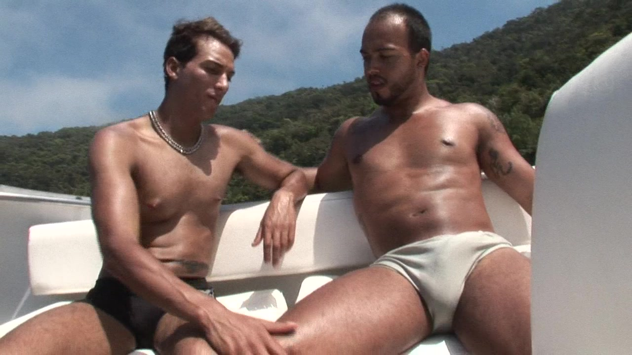 Two tanned gays please each other's butt on a yacht